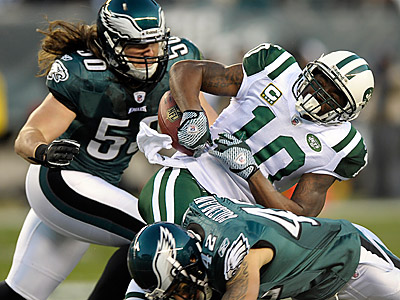 Santonio Holmes fumbles as Kurt Coleman (bottom) and Casey Matthews make the tackle. (Michael Perez/AP Photo)
