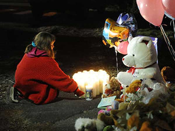 Balancing rights: A girl lights candles at a memorial in Newtown, Conn., a day after the massacre.  (Olivier Douliery/Abaca Press/MCT)