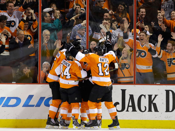 Flyers players celebrate with Claude Giroux after he scored a goal during the third period of an NHL hockey game against the Columbus Blue Jackets, Thursday, Dec. 19, 2013, in Philadelphia. Philadelphia won 5-4. (Matt Slocum/AP)