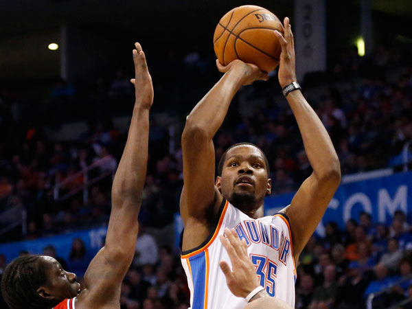 Thunder forward Kevin Durant (35) shoots over Chicago Bulls forwards Tony Snell (20) and Carlos Boozer (5) during the fourth quarter of an NBA basketball game in Oklahoma City, Thursday, Dec. 19, 2013. Oklahoma City won 107-95. (Sue Ogrocki/AP)