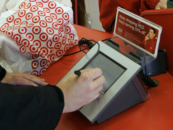 A customer signs his credit card receipt at a Target store. The massive data breach at Target last week has again highlighted how the United States remains a relatively insecure backwater when it comes to credit card technology. (AP Photo/Phil Coale, File)