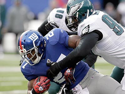Antonio Dixon tackles Brandon Jacobs in the first quarter of the Eagles´ 38-31 win over the Giants. (Yong Kim / Staff Photographer)