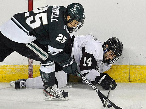 Michigan State´s Brent Darnell, left, and Union College´s Shayne Gostisbehere, right, fight for control of the puck during the second period of an East regional semifinal game in the NCAA college hockey tournament in Bridgeport, Conn., Friday, March 23, 2012. (AP Photo/Jessica Hill)