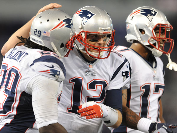 Patriots quarterback Tom Brady, celebrates with teammates LeGarrette Blount, left, and Aaron Dobson after Blount scored a touchdown in the second half of an NFL football game against the Baltimore Ravens, Sunday, Dec. 22, 2013, in Baltimore. (Gail Burton/AP)
