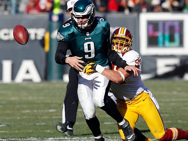 The Eagles´ Nick Foles fumbles the football against Washington Redskins´ Ryan Kerrigan. (Yong Kim/Staff Photographer)