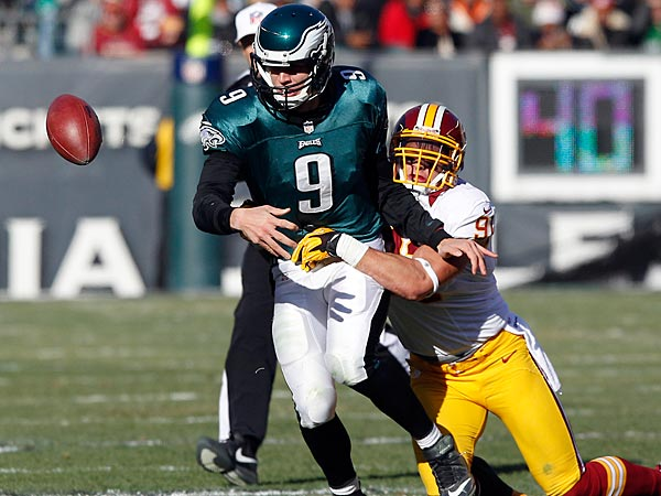 Eagles quarterback Nick Foles fumbles the football against the Washington Redskins´ Ryan Kerrigan during the first quarter on Sunday, December 23, 2012. (Yong Kim/Staff Photographer)