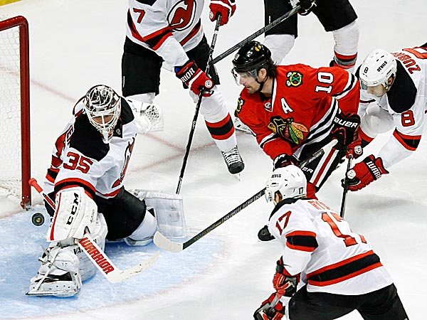 Devils goalie Cory Schneider makes a save on a shot by Blackhawks left wing Patrick Sharp as Mark Fayne, Dainius Zubrus, and Michael Ryder also defend. (Charles Rex Arbogast/AP)