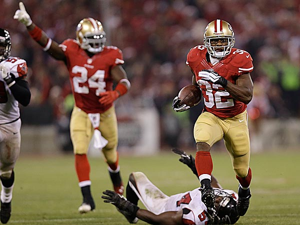 49ers running back Kendall Hunter runs past Falcons outside linebacker Stephen Nicholas for a long gain as Anthony Dixon celebrates. (Marcio Jose Sanchez/AP)