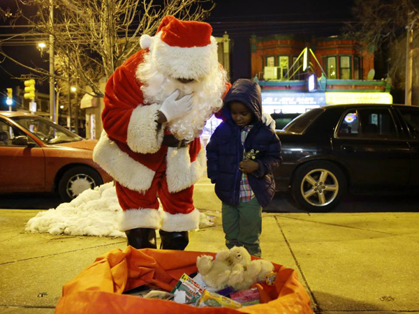 Paul Moore, left, dressed as Santa Claus, looks over a bag of toys with Dante Wright, 5, as Moore hands out holiday gifts to children at the Philadelphia Police Department´s 12th district station in Philadelphia on Wednesday, Dec. 18, 2013. (AP Photo/Matt Slocum)