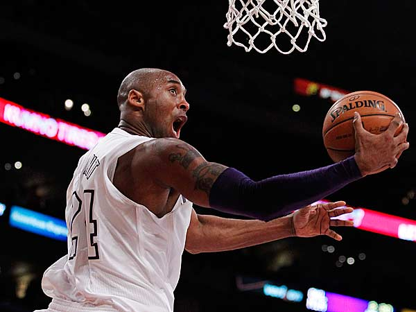 Los Angeles Lakers guard Kobe Bryant (24) shoots a reverse lay up between New York Knicks center Tyson Chandler, left, and forward Carmelo Anthony, right, during the first half of their NBA basketball game in Los Angeles, Tuesday, Dec. 25, 2012. (Alex Gallardo/AP)