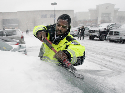 Deptford Mall security officer Shayne Beckford sweeps snow and ice off of a shoppers car at the Deptford Mall on Sunday. (Elizabeth Robertson / Staff Photographer)