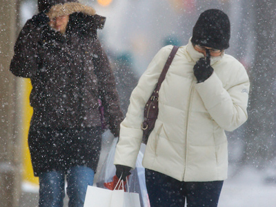 Sisters Lisa and Debbie Fisher of Havertown make their way through Sunday afternoon´s snow at Suburban Square in Ardmore. (Ed Hille / Staff Photographer)