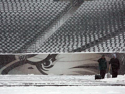 Workers move snow inside Lincoln Financial Field as snow falls on the<br />field yesterday. (Yong Kim/Staff Photographer)