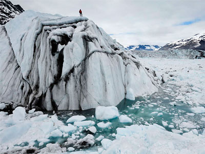 Atop an iceberg in Columbia Bay, Alaska, is Extreme Ice Survey field technician Adam LeWinter, June 2008.