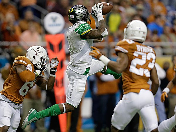 Oregon´s Josh Huff pulls in a pass as Texas´ Quandre Diggs defends. (Eric Gay/AP)