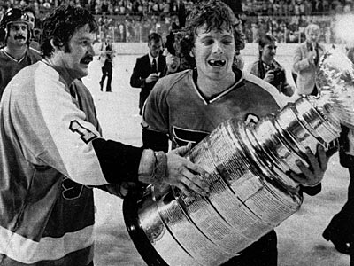 Bobby Clarke and Bernie Parent carry the Stanley Cup in 1975. (AP File Photo)