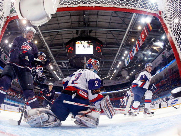 Members of the United States junior team, at left, watch a goal scored by USA´s Jake McCabe, not seen, on Slovakia goalie Adam Nagy, center, during the first period of an IIHF World Junior Championships hockey game, Monday, Dec. 31, 2012, in Ufa, Russia. (Mark Blinch/AP)