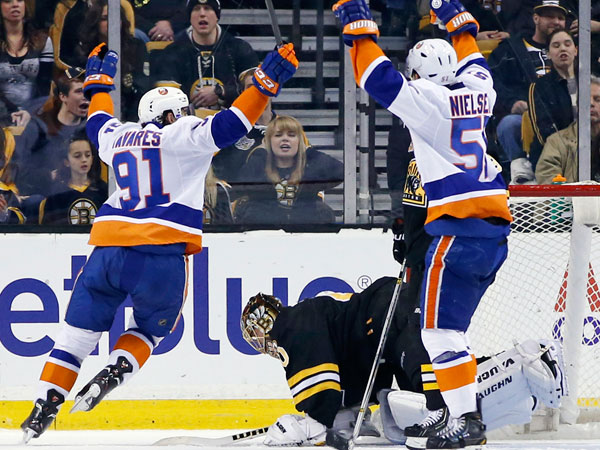 Islanders center John Tavares (91) and New York Islanders center Frans Nielsen (51) celebrate a goal over Boston Bruins goalie Tuukka Rask, bottom, during the second period of an NHL hockey game in Boston, Tuesday, Dec. 31, 2013. (Elise Amendola/AP)