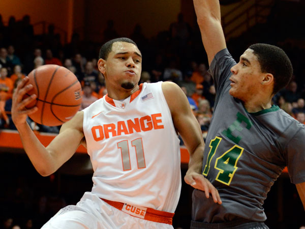 Syracuse´s Tyler Ennis, left, passes around Eastern Michigan´s Karrington Ward during the second half of an NCAA college basketball game in Syracuse, N.Y., Tuesday, Dec. 31, 2013. Syracuse won 70-48. (Kevin Rivoli/AP)