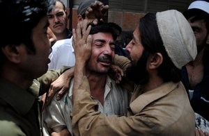 People comfort a family member of a female polio worker who was killed in northwest Pakistan on Tuesday. (Mohammad Sajjad / AP)