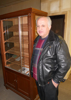 Willy Bouikidis next to a cigar case left behind in his restaurant space at 1518 Sansom St.