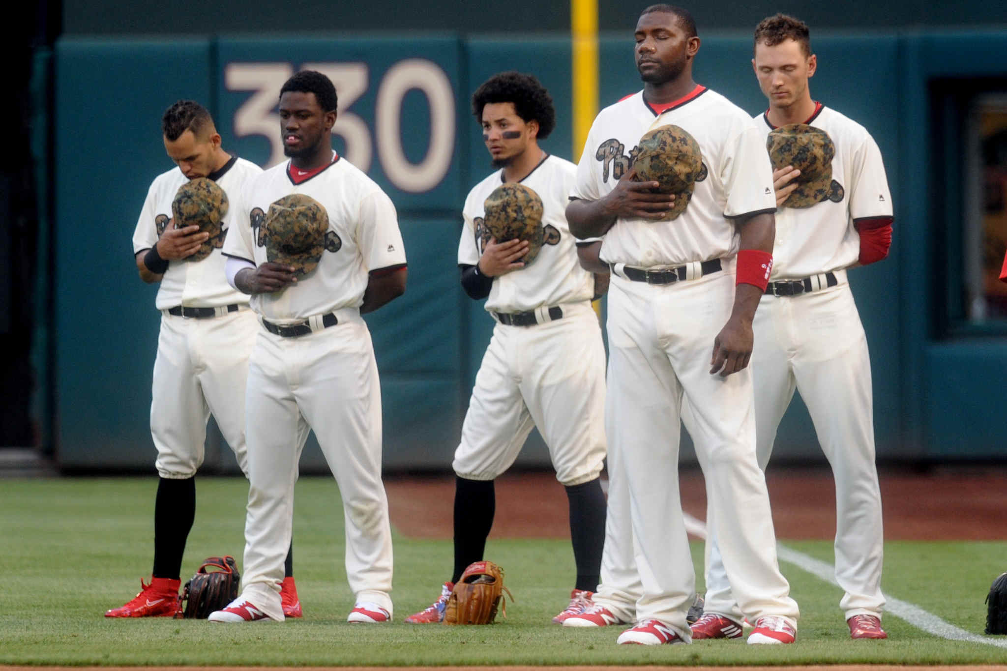 Howard (second from right) stands with teammates for the National Anthem before their game with the Nationals, holding their camouflage-designed caps over their camo jerseys in commemoration of Memorial Day.