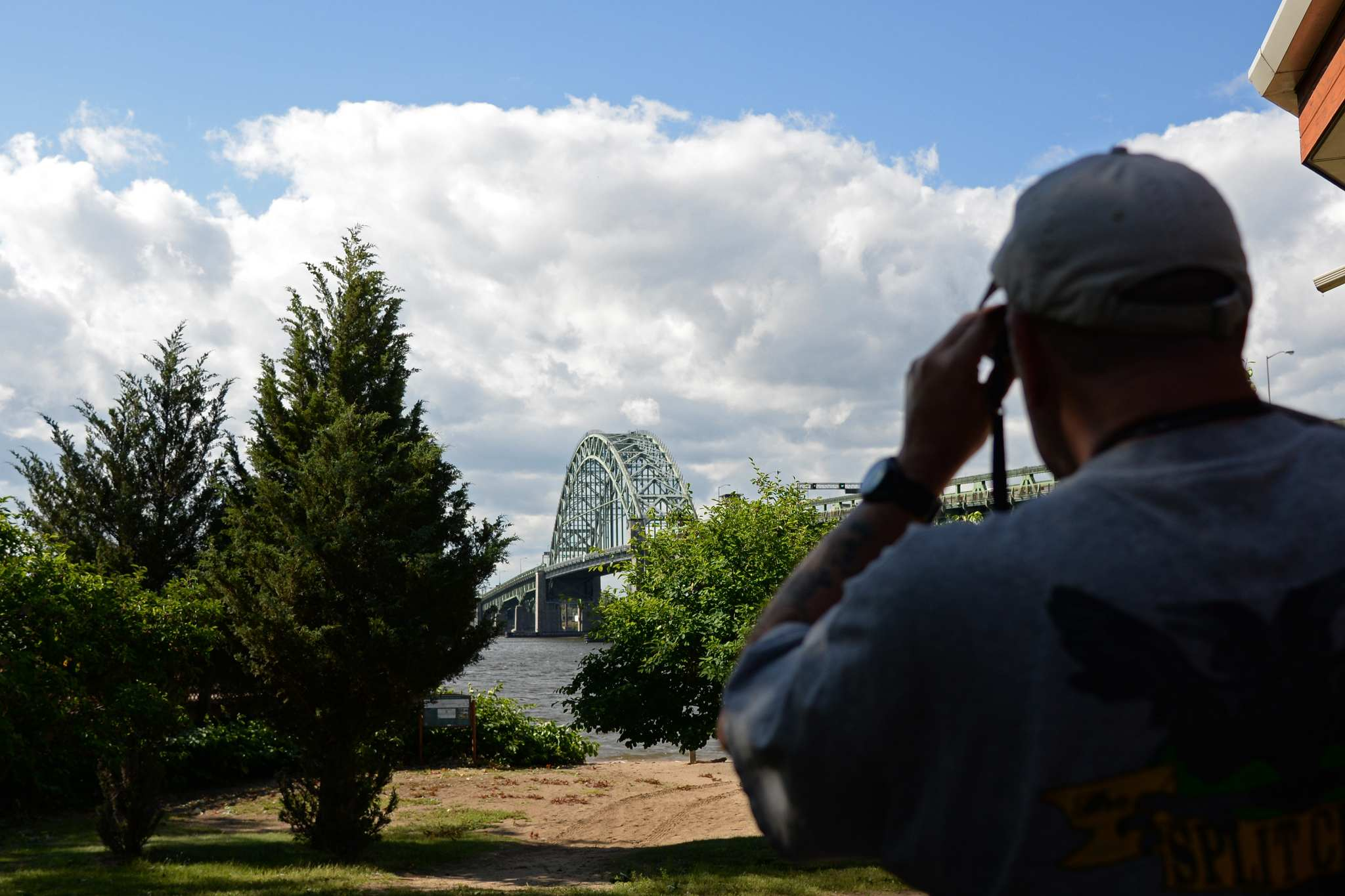 Clyde Croadale, a teaching assistant at Palmyra Cove Nature Park uses his binoculars to look at peregrine falcons nesting on the top of the Talcony Palmyra Bridge.