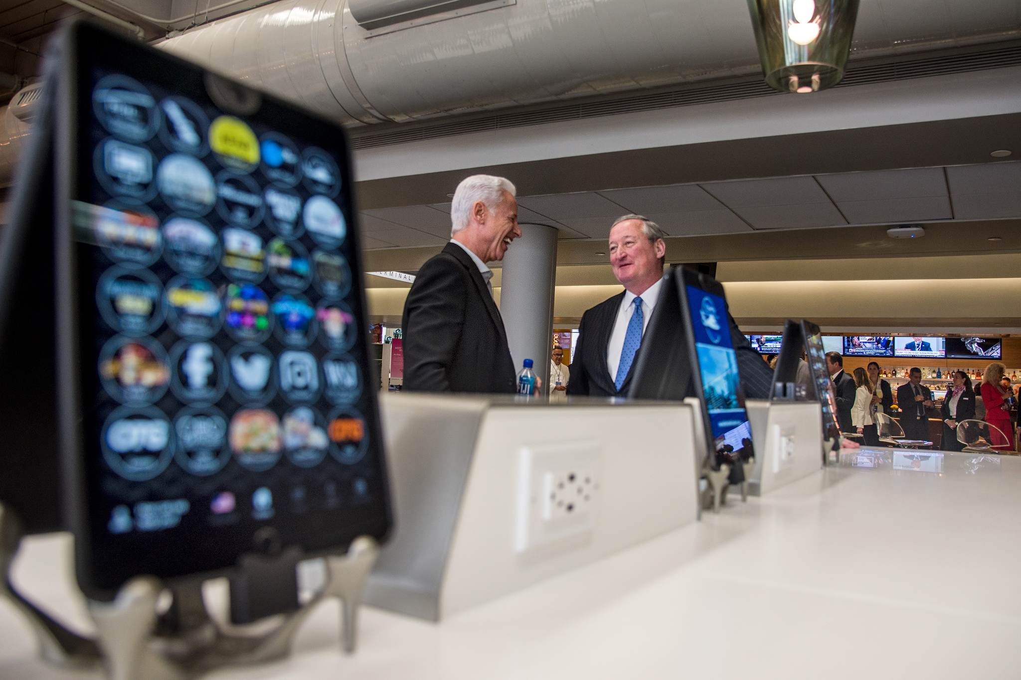 Among a few of the thousands of Terminal B's newly-installed iPads, Mayor Kenney (right) talks with Rick Blatstein, OTG founder and CEO, before Monday's ribbon cutting at PHL.