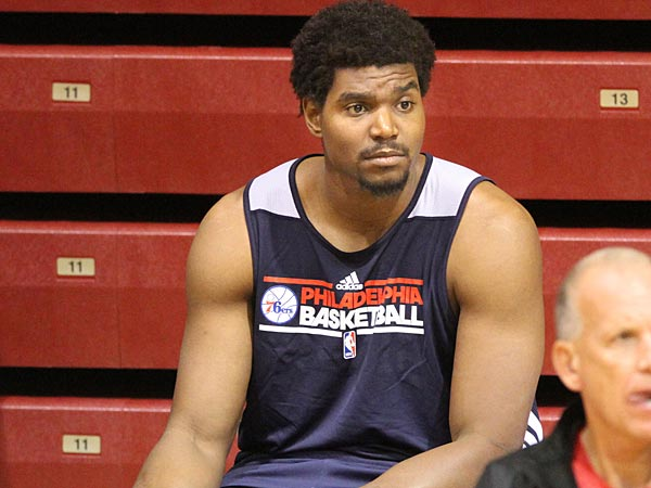 Andrew Bynum, center, the 76ers major off-season acquisition, rubs his<br />right knee as he sits behind Head Coach Doug Collins,  right.  The<br />76ers opened training camp today Oct. 2, 2012. 76ers center Andrew<br />Bynum will sit out three weeks as a precaution after receiving knee<br />treatment in Germany. Bynum had injections of plasma-rich platelets<br />that supposedly stimulate healing in arthritis-affected areas in both<br />of his knees.   ( Charles Fox / Staff Photographer )