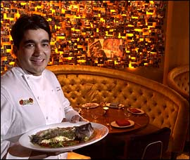 Chef Jose Garces with El Vez´s snapper. He starts with the traditions and recipes of authentic Mexican cooking, then retools things for a new vision and polish.                                      (Jonathan Wilson/Inquirer)