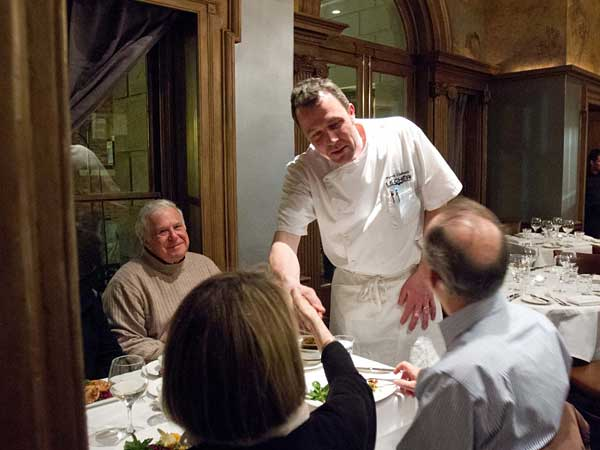 Chef Pierre Calmels visits with guests dining at Le Cheri.  ( DAVID M WARREN / Staff Photographer )