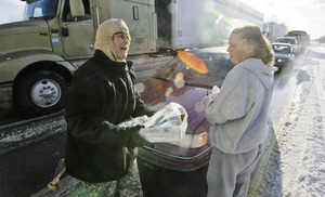 Deborah Miller (right) , of Rhode Island, speaks with Andrea Bryer of the Pennsylvania National Guard on I-78 in Bethel, Pa. Huge - perhaps record - amounts of sleet left drivers icebound.