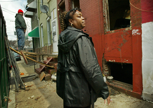 Barbara Stevenson-Foster examines rowhouse under demolition that is attached to her house.