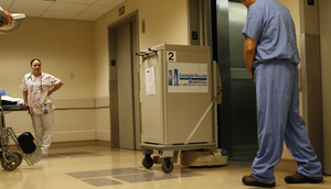 "A courier robot on a supply run prepares to enter an elevator at Lehigh Valley Hospital in Allentown. Peter Seiff, an executive with the robot's maker, Aethon, said robots seem slow, but humans stop for talk, a drink, food. His company's studies show the machines get more done in the long run. ""It's a classic case of tortoise and hare,"" he said."