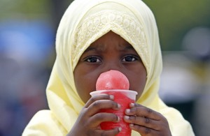 Three-year-old Kharima Muhammad cools off with an ice treat during the festival at Penn's Landing.