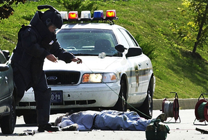 An Erie bomb-squad technician works to turn over the body of Brian Wells after the pizza deliveryman was killed when an explosive device strapped to his neck exploded. Wells told police before the blast that he was an innocent victim. The incident occurred on Aug. 28, 2003.