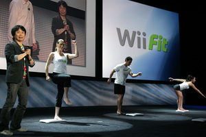 With not a couch in sight, Nintendo game designer Shigeru Miyamoto (left) introduces the pressure-sensitive balance board for the new exercise game, Wii Fit. The idea is to combine workouts with video play.