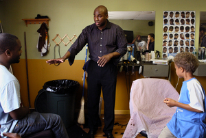 At Rob's Barbershop on Haverford Avenue, Dr. Keith Leaphart (center) talks with an unidentified man and 6-year-old Dylan Green. He says that barbers should be counselors to the young.