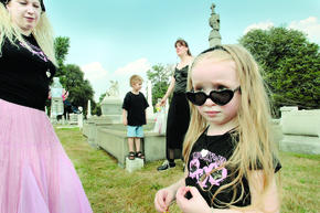 "Growing up goth: Lynnea Ranelli-Del Rosario keeps an eye on daughter Faith Eternity, 4, during playtime at Laurel Hill Cemetery. Behind them are friend Jennifer Holtzinger with son Joe, 7. Now that she's a goth mom, Ranelli-Del Rosario has ""mellowed out"" her look to eliminate the black leather and PVC. ""Turns out, you can still look goth and be in pink!"""