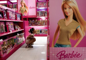 A girl looks at Barbie dolls in Beijing.