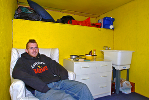 All the comforts of home. Chris Harne relaxes in his living room/kitchen/bedroom. Some furniture is secondhand while other items are from a dump or his junk job.