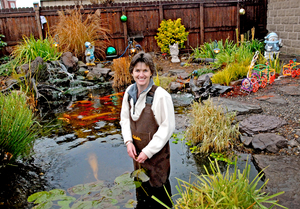 "Donning waders, Diane Schweizer stands in her 5,000-gallon fish pond, which is her passion.""It's like my getaway. . . . Some people watch TV or sew. I like to take care of my pond."""
