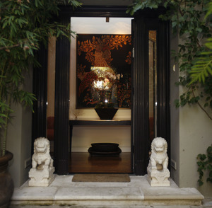 Jerome Dahan and Lela Tillem's Moroccan entryway , framed by bamboo and foo dogs and bougainvillea, opens to a tapestry by French surrealist painter Jean Lurçat. The 1927 Mediterranean-style home is in Santa Monica.