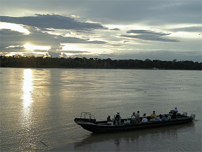 A skiff at sunset. Rivers are the Amazon's roads, and a stream of vessels passed La Amatista — ferries, dugout canoes, rafts, barges, tankers, carrying people, plantains, vehicles and crude oil. (William Ecenbarger/For The Inquirer )