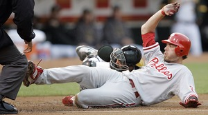 Jayson Werth slides past Athletics catcher Kurt Suzuki to score a first-inning run last night in Oakland.