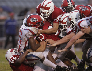 Neshaminy´s Quilan Arnold (in Skins helmet) is brought down against Souderton last week. No. 4-ranked Souderton is 2-0 and will take on Roman Catholic tonight.