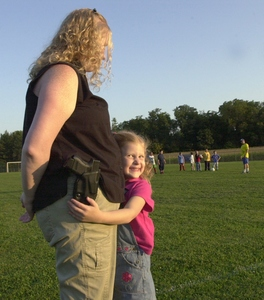 Meleanie Hain gets a hug from daughter Isabella at the soccer field at Optimist Park in Lebanon, Pa. The mother upset other parents by bringing a loaded Glock 26 to a recent game.