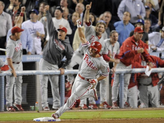 Shane Victorino raises his fist as he rounds first base after hitting a home run to tie Game 4 of the NLCS in Los Angeles on Oct. 13. The Phils won, 7-5.