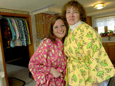 Finding hospital robes humiliating, Brenda Jones (right) created Hug Wraps. She and niece Carie Gordon model them at Jones´ house in Southampton, Burlington County. (April Saul / Staff Photographer)