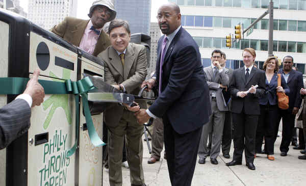 Mayor Nutter (right) and Councilman Frank DiCiccocut the ribbon on a new solar- powered trash bin at thecorner of 15th Street and JFK Boulevard.